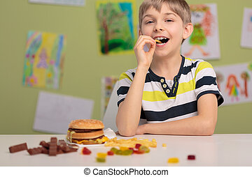 Kid and unhealthy snacks - Cheerful kid at school eating...
