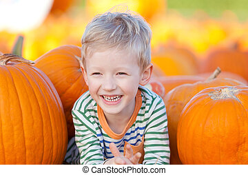 cute smiling boy having fun at the pumpkin patch