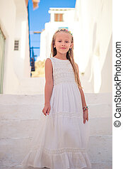 Kid at street of typical greek traditional village with white walls and colorful doors on Mykonos Island