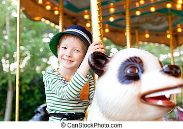 kid at the merry-go-round - cheerful smiling little boy...