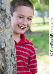 Kid behind a tree in a park