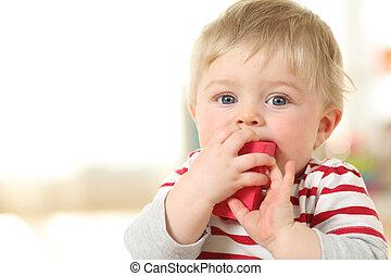 Kid biting a toy looking at camera