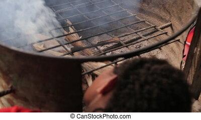 Kid Blowing Air Into Fire - Handheld, medium close up shot...