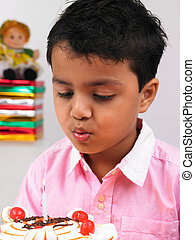 kid blowing candle on birthday cake