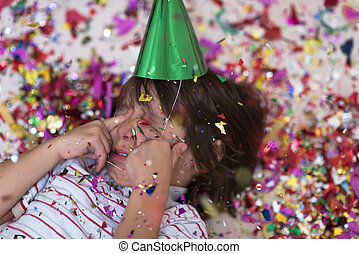 kid blowing confetti while lying on the floor