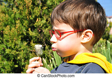Kid blowing dandelion
