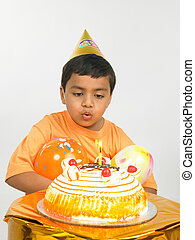 kid blowing the candle on his cake