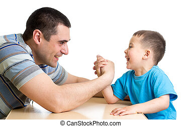 kid boy and his dad competing in physical strength