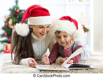 kid boy and his mom reading book at Christmas