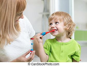 Kid boy brushing teeth in bathroom. His mother monitoring accuracy and time of cleaning action with hourglass.