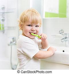 Kid boy brushing teeth in bathroom
