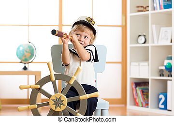 Kid boy dressed captain or sailor plays on chair as ship in his room. Child looks through telescope.