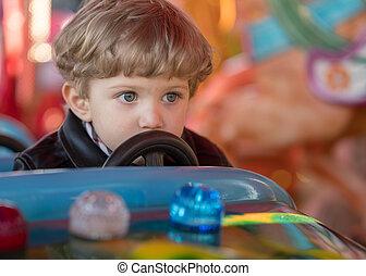 Kid boy drives a blue car at carousel