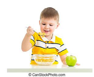 kid boy eating corn flakes with milk