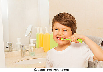 Kid boy happy to brush teeth in the morning