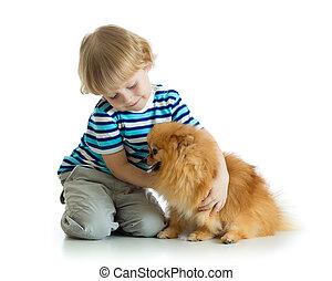 Kid boy hugging dog spitz isolated on white background