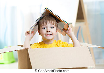 kid boy playing in a toy house in nursery
