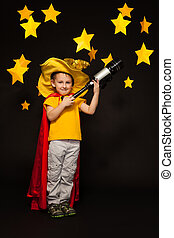 Kid boy playing sky watcher with a telescope