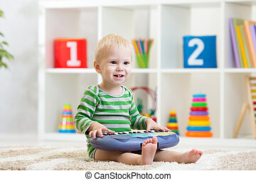 Kid boy playing toy piano in nursery