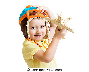 kid boy playing with wooden airplane toy and dreaming about pilo