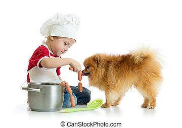 Kid boy plays chef with dog. Child weared cook feeds Spitz puppy.