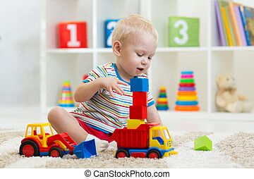 kid boy toddler playing with toy car in nursery