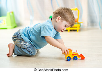 kid boy toddler playing with toy car indoors