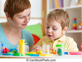 Kid boy with teacher play clay at home, kindergarten, daycare center or playschool