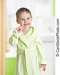 kid brushing teeth in bathroom