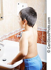 Kid brushing teeth looking to mirror