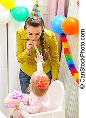 Kid celebrating first birthday with mother