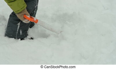 Kid cleaning snow with toy spade - Little child trying to...