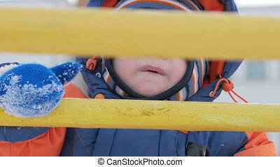 Kid climbs on metal hill in winter. Mom helps son. Boy warmly dressed in overalls, he was about a year. Concept winter Activity
