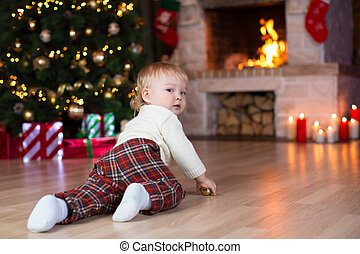 kid crawling to gifts lying under Christmas tree