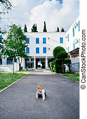 Kid crawls on the asphalt against the background of a white building and green trees