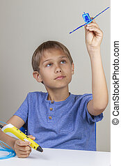 Kid creating with 3d printing pen and enjoy his new blue plane