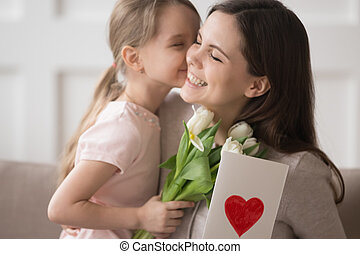 Kid daughter holding flowers kissing congratulating mom with mothers day