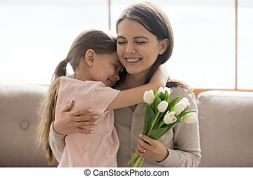 Kid daughter hugging mom holding tulips congratulating with mothers day