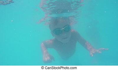Kid diving in blue water of swimming pool - Underwater shot...