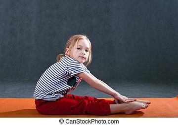 Kid doing fitness yoga exercises