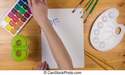 Kid draw greeting card on white paper for mothers day, stop motion animation, top view