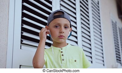 Kid dressed in cap and t-shirt wearing white headphones is listening to good song from a smartphone isolated on white background. Portrait of a cute boy who listens to the good music