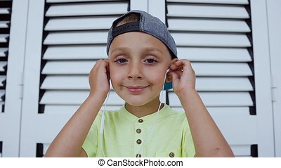 Kid dressed in cap and t-shirt wearing white headphones is listening to good song from a smartphone isolated on white background. Portrait of a cute boy who looks at the camera and listens to the good music
