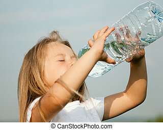 Kid drinking water from a bottle against a sky background