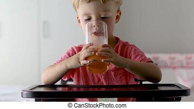 Kid drinking orange juice at home - Little boy with oranges...