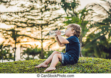 Kid drinking pure fresh water in nature at sunset