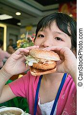 Kid eating - A Chinese little kid eating hamburger