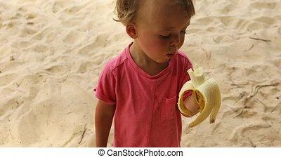Kid eating banana on beach - Adorable child biting tasty...