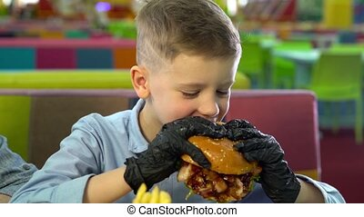 Kid eating burger in black gloves and looking at the camera...