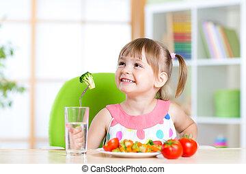 Kid eating healthy vegetables meal in home or nursery